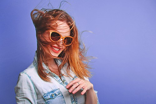 Woman with sunglasses smiling on a blue background