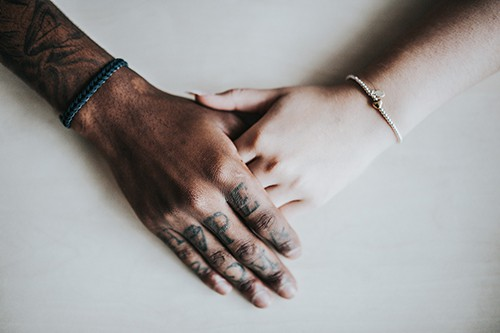 Man's tattooed hand holding a woman's hand