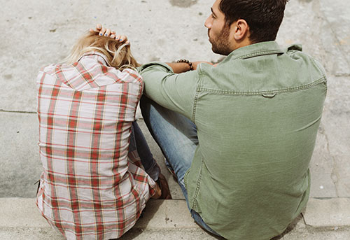 Woman and man sitting on the street