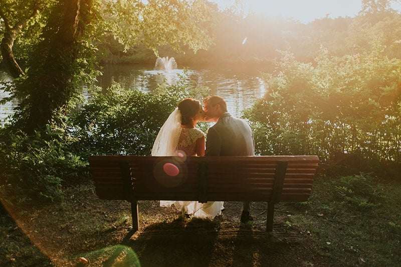 Married couple kissing on a bench by the river
