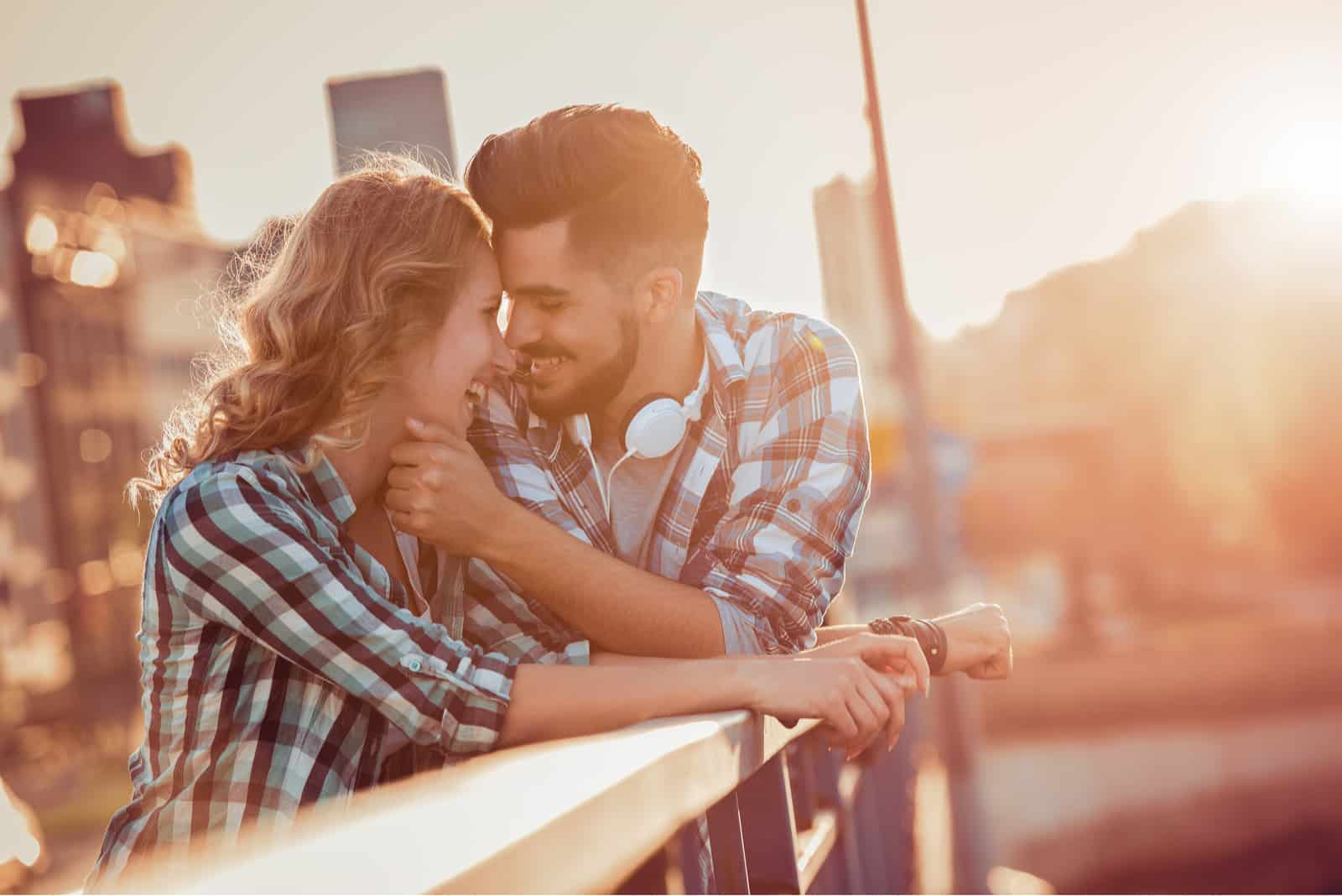 a man and a woman embrace on the bridge