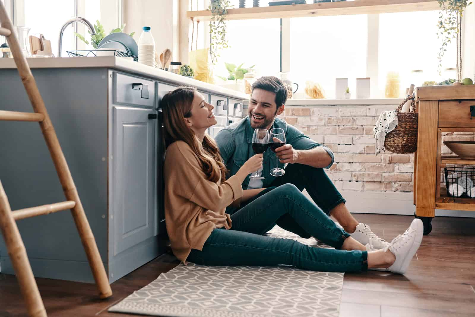 a smiling couple sitting on the floor drinking wine