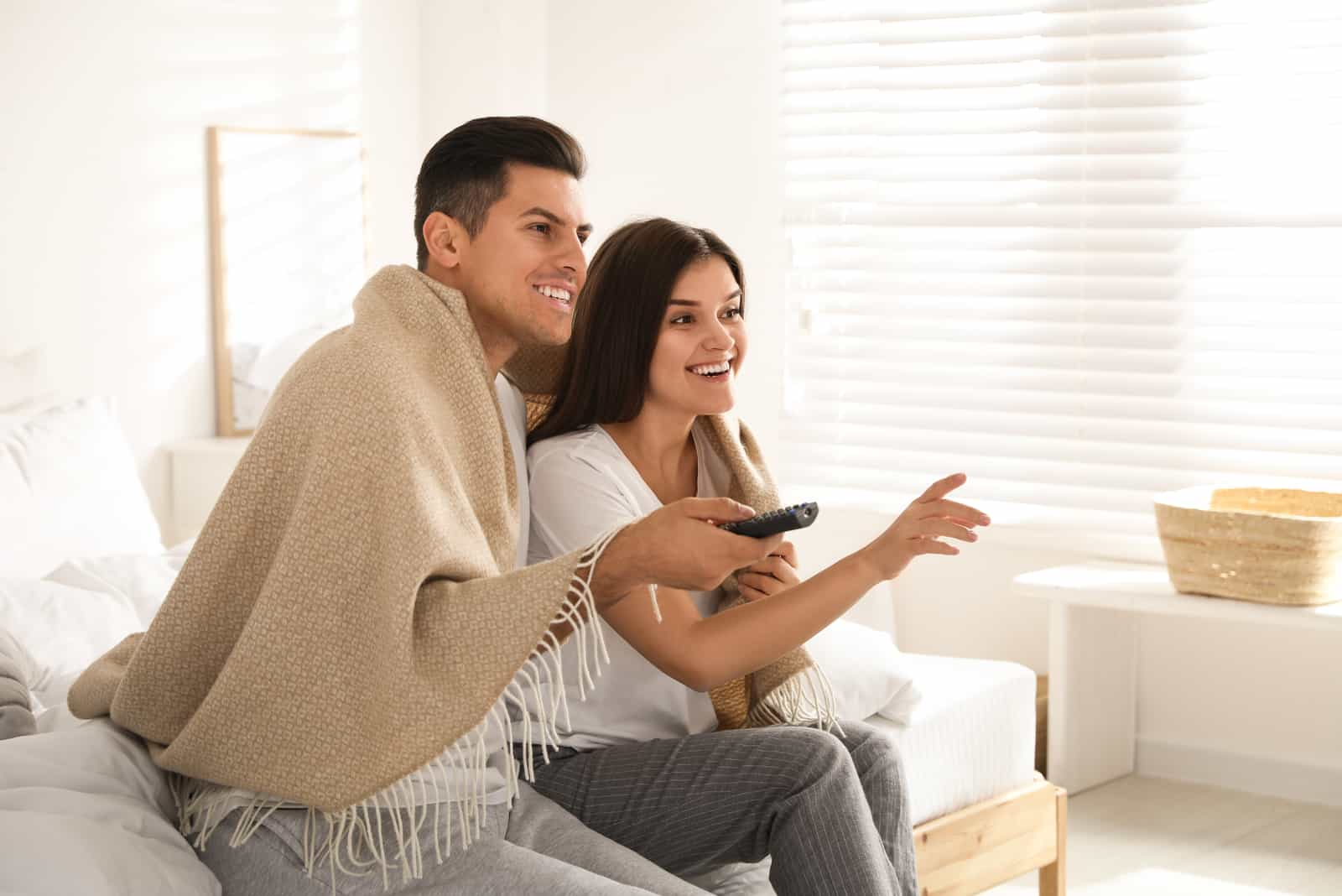a smiling man and woman sit on the couch and watch tv