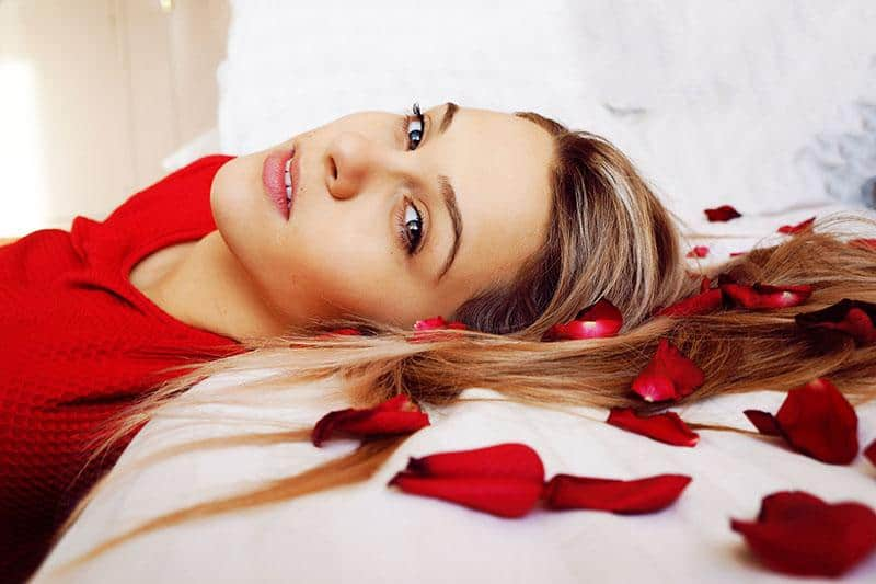 Woman leaning on bed with rose petals on it
