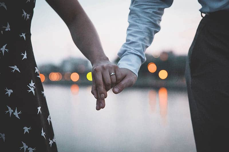 Woman holding man's hand