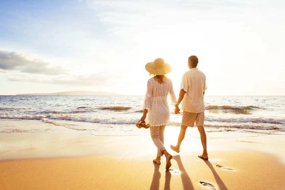 a romantic couple walking barefoot on the beach at sunset