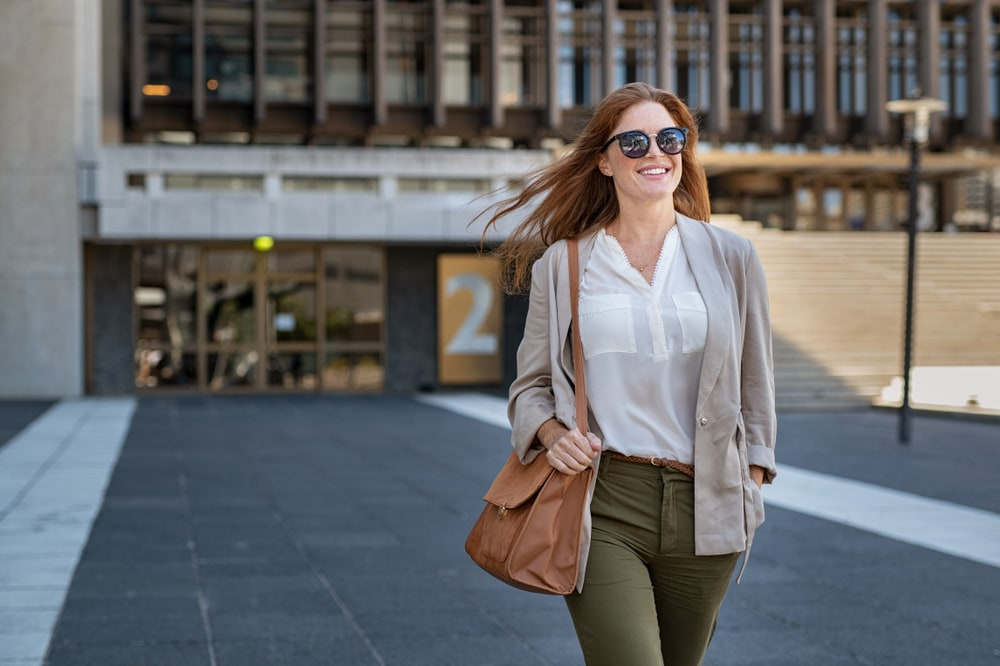 a smiling beautifully dressed woman with sunglasses walks down the street