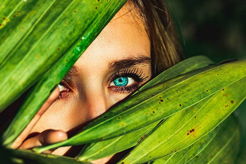 Blue eyed woman hiding behind leaves