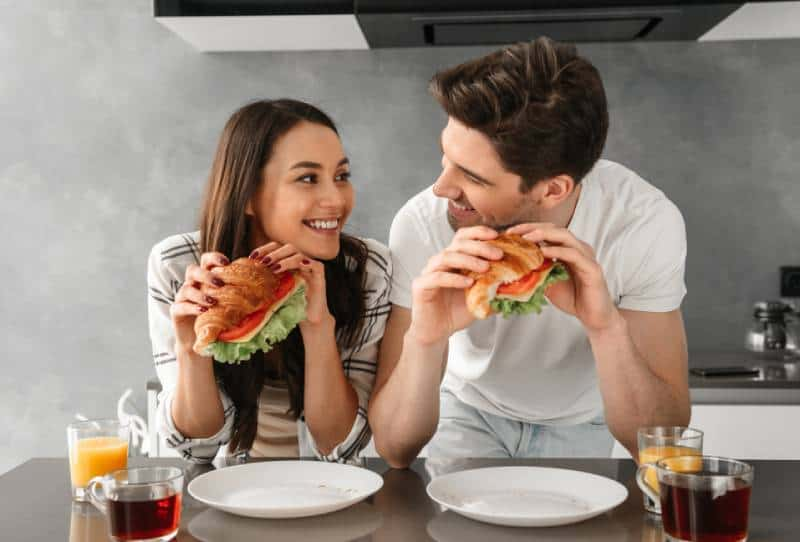 couple looking at each other and smiling while eating sandwiches