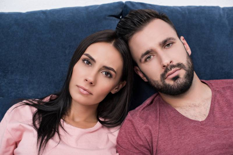 emotionless young couple leaning against each other while sitting on the couch