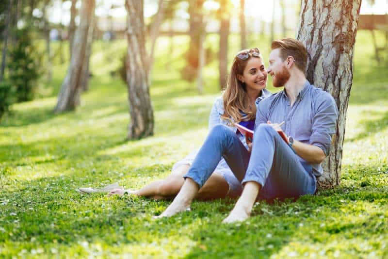 lovely couple sitting on grass and leaning on tree