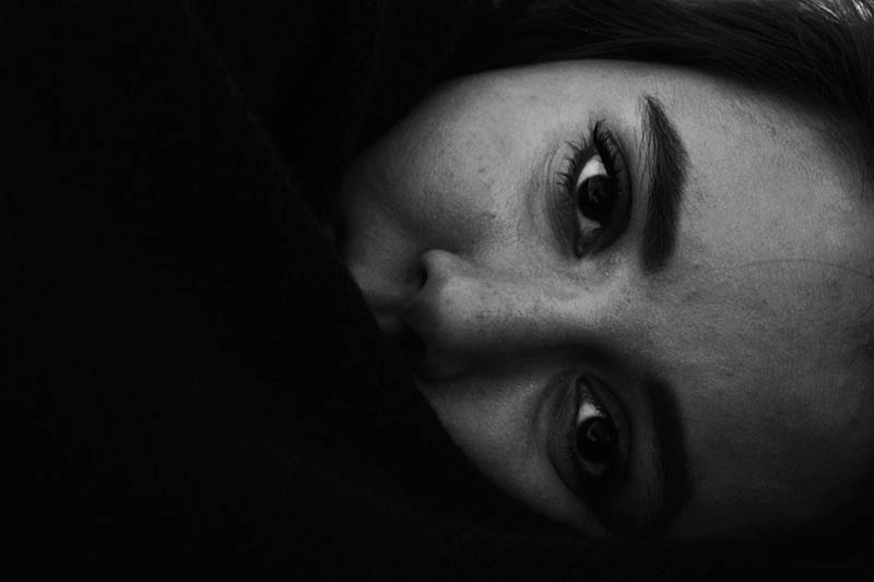 Half of woman's face covered with blanket