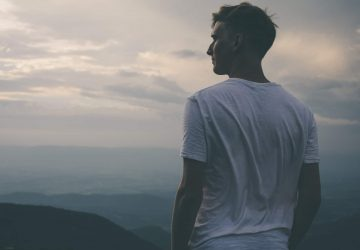Young man standing facing mountains during sunset