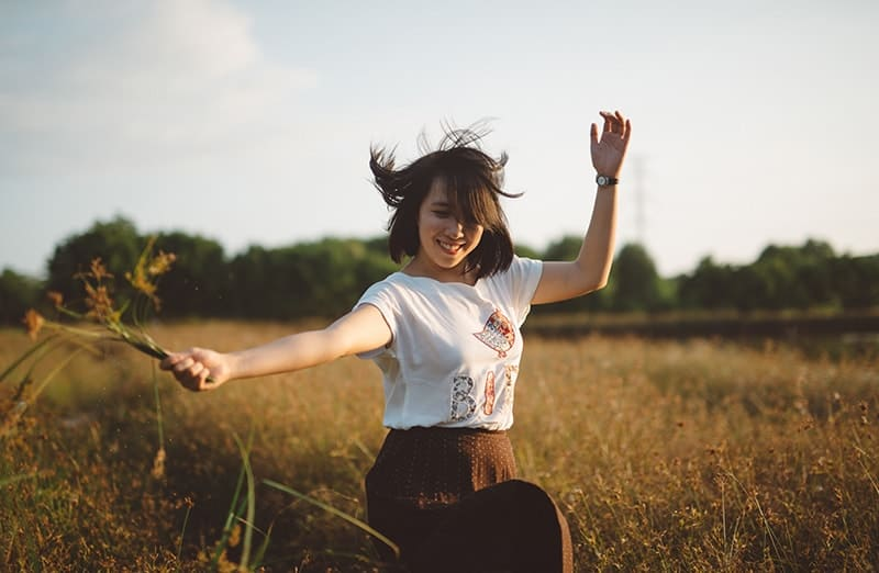 Girl dancing in a meadow with flowers in her hand