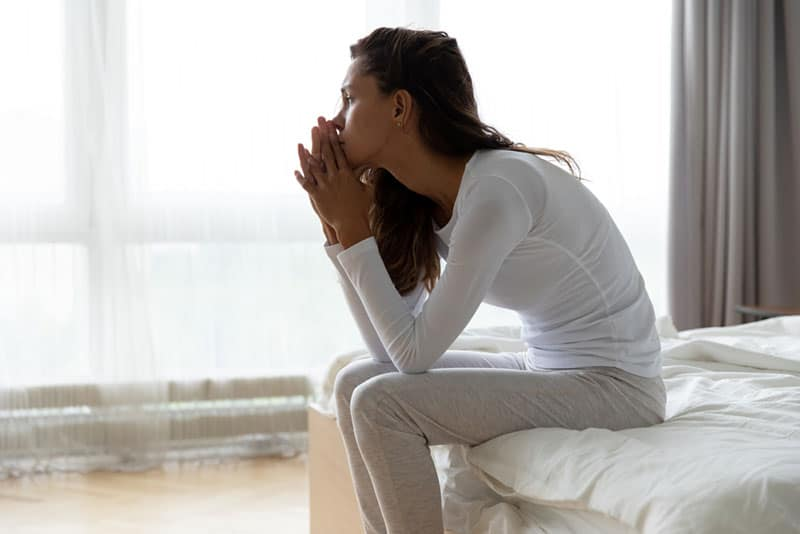 sad young woman sitting on the bed and looking at distance