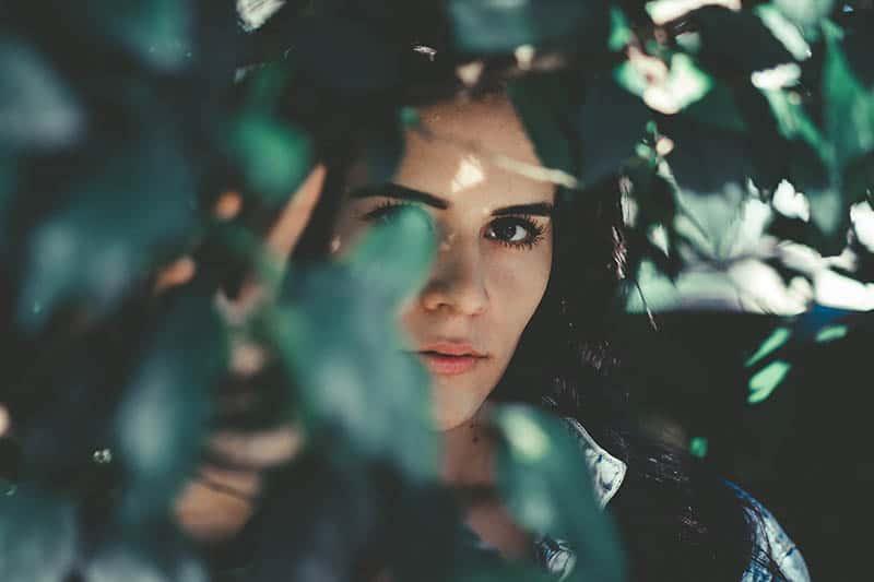 Woman hiding behind leaves