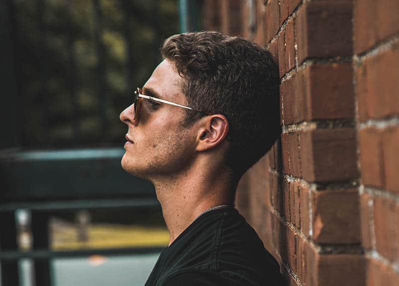 Man with sunglasses leaning his head against wall
