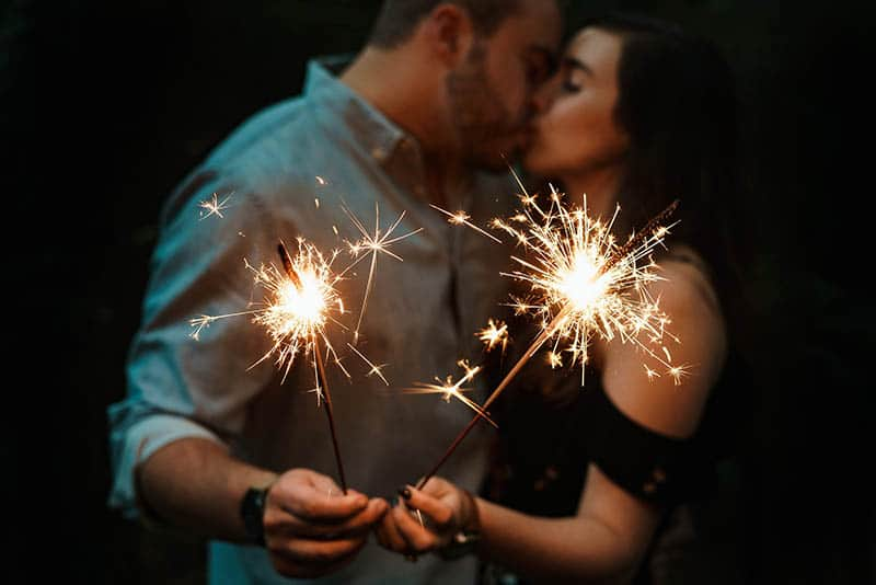 Couple kissing with sparklers in their hands