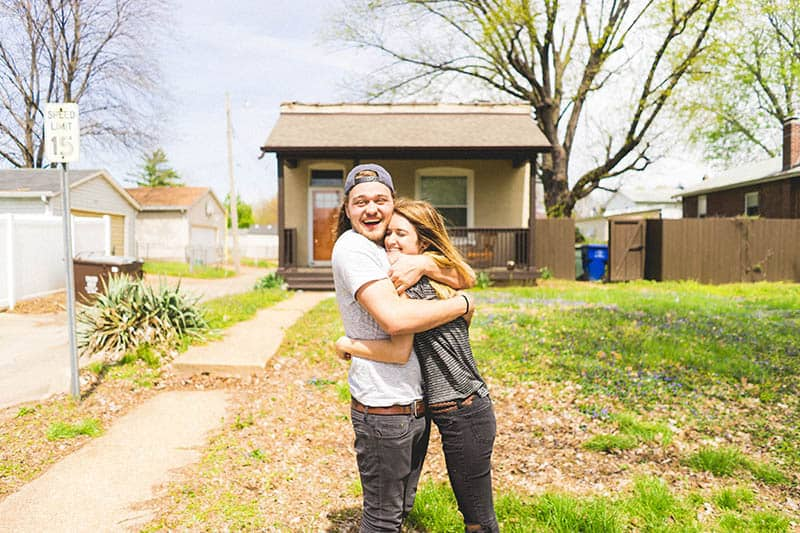 Happy couple hugging in front of a house