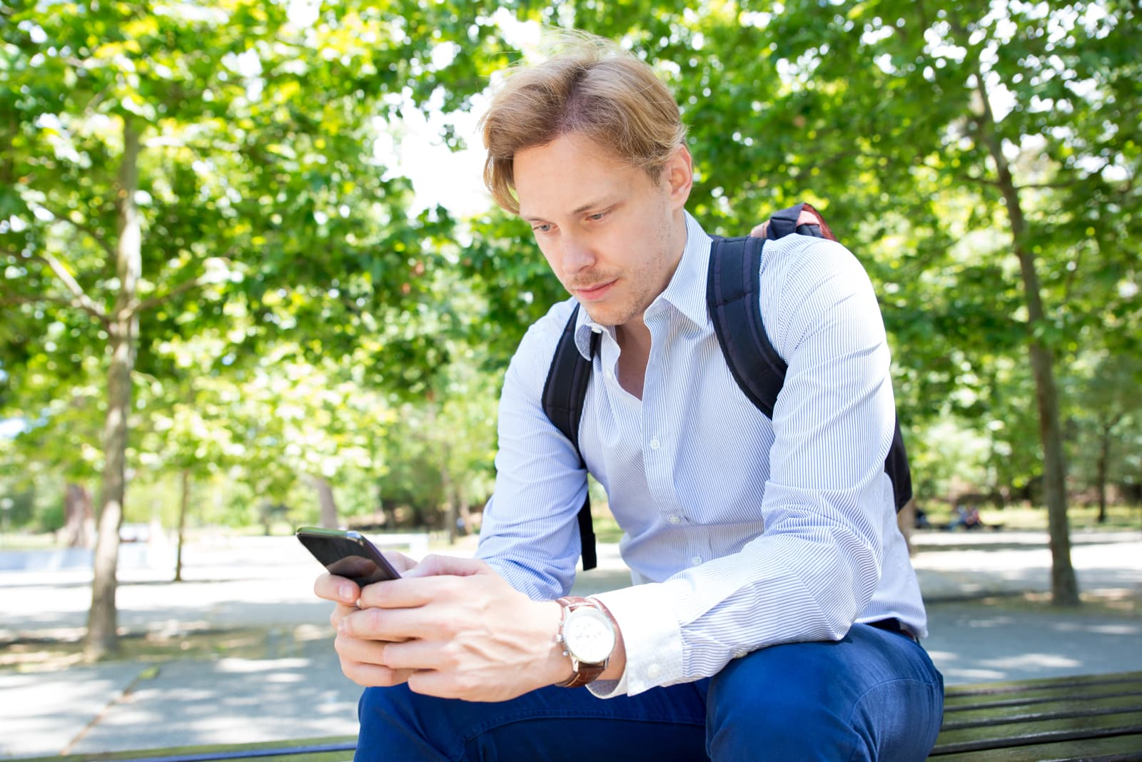 man sitting and holding his phone