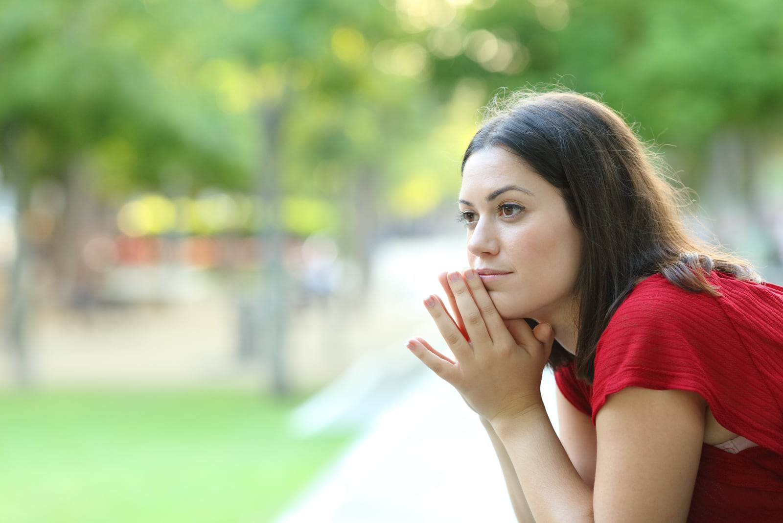 pensive woman sitting on a bench in a park