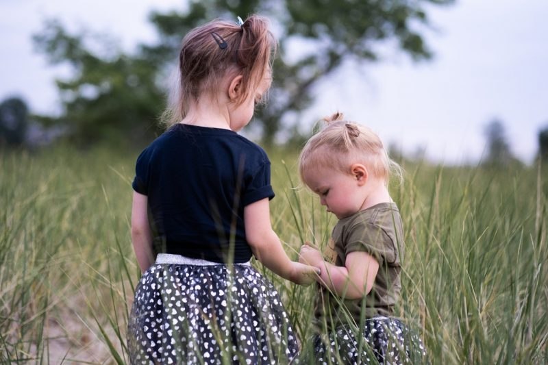 two little girls standing in the field