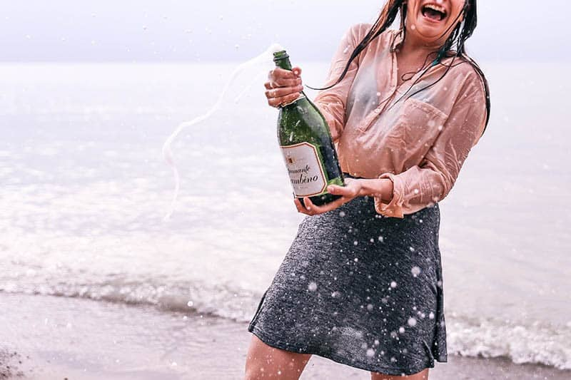 Woman celebrating with champagne on beach