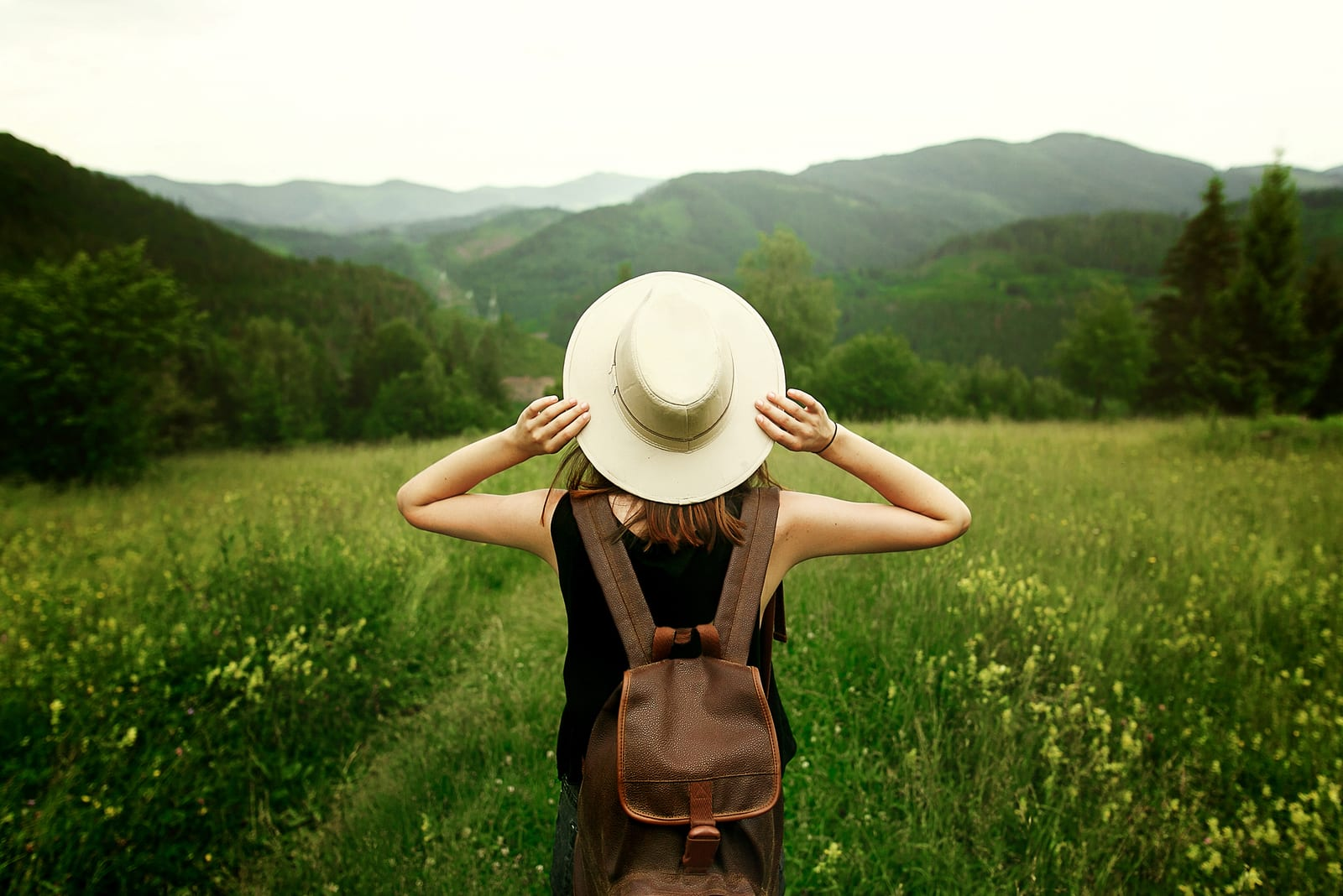 woman traveler with backpack holding hat and looking at amazing mountains