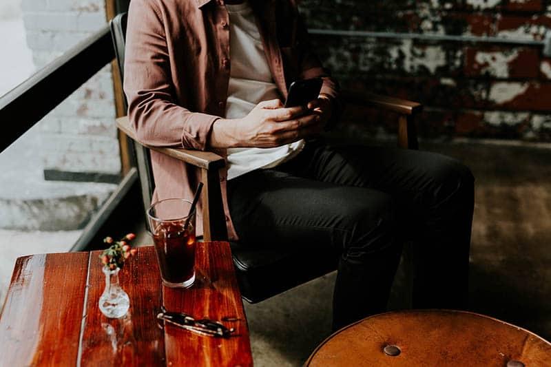 Man at a bar typing on phone