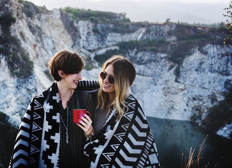 Two women smiling at each other at a viewpoint