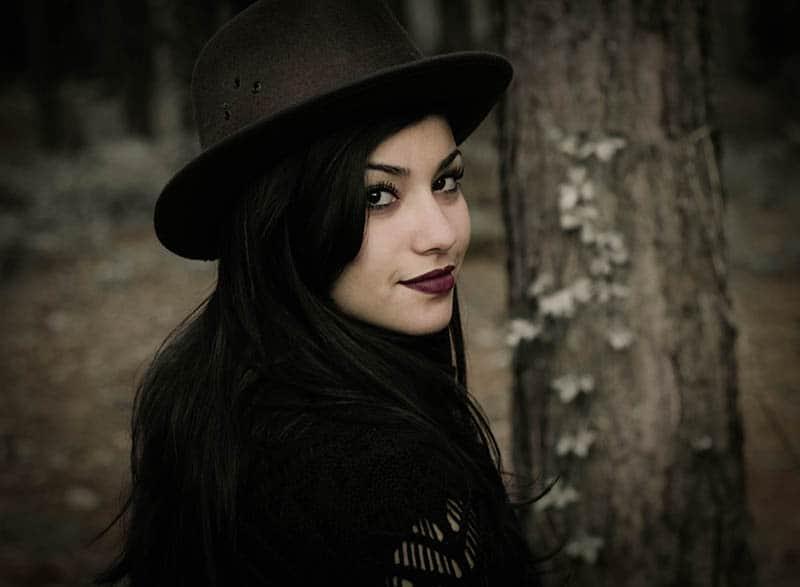 Woman in the woods looking over her shoulder