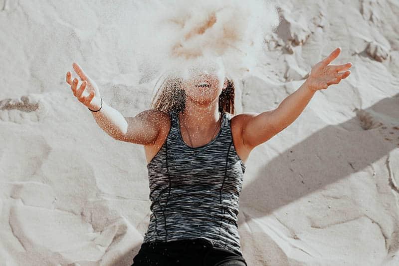 Girl throwing beach sand on herself