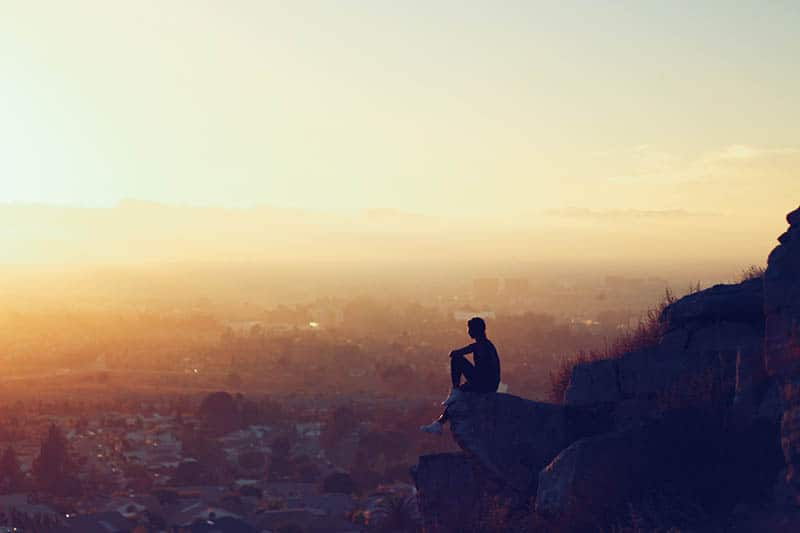 Girl sitting on a viewpoint looking at the city