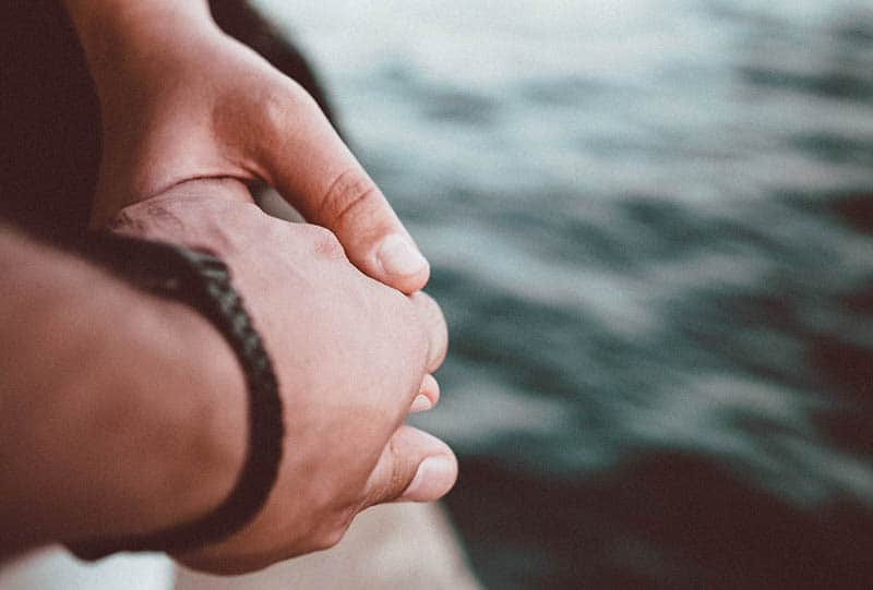 close up photo of couple holding hands