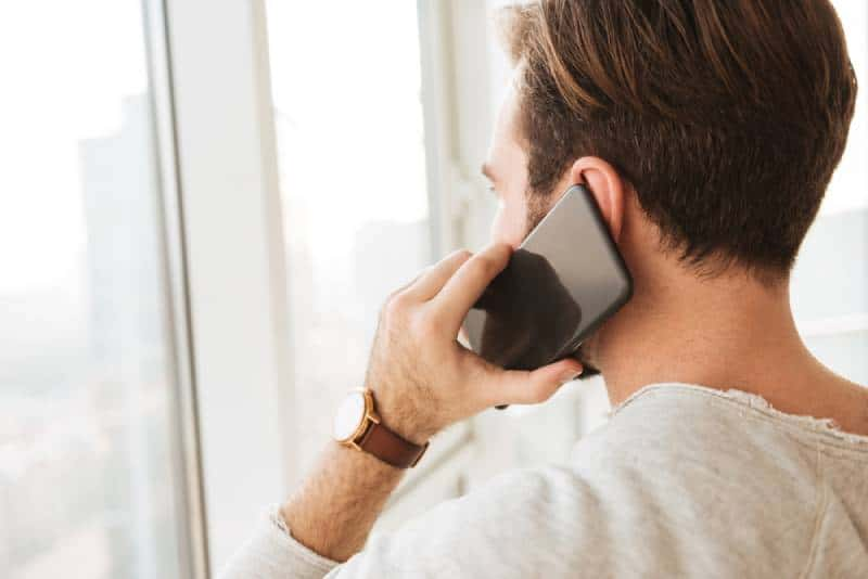 closeup photo from back of man talking on phone and looking through window
