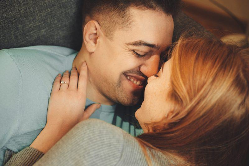 couple lying on couch kissing and smiling