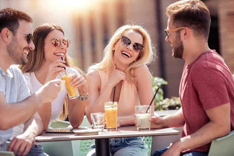 group of smiling friends talking in cafe street
