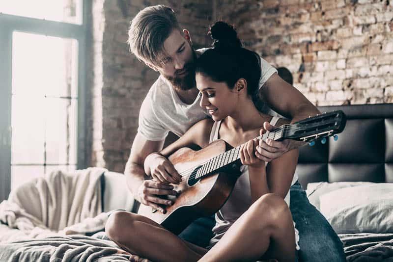 man teaching woman to play a guitar