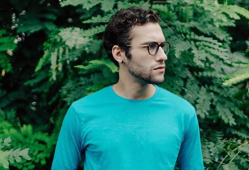 man wearing glasses and blue long sleeve shirt standing outside