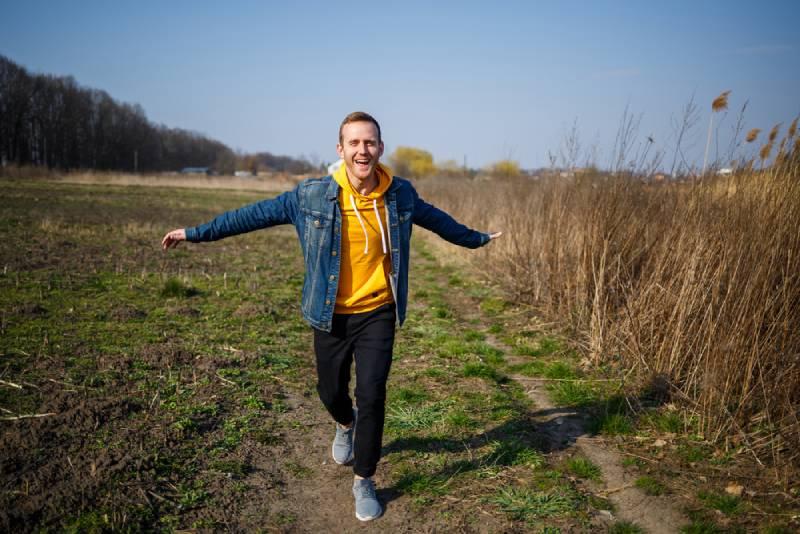 smiling man enjoying wind blowing in nature