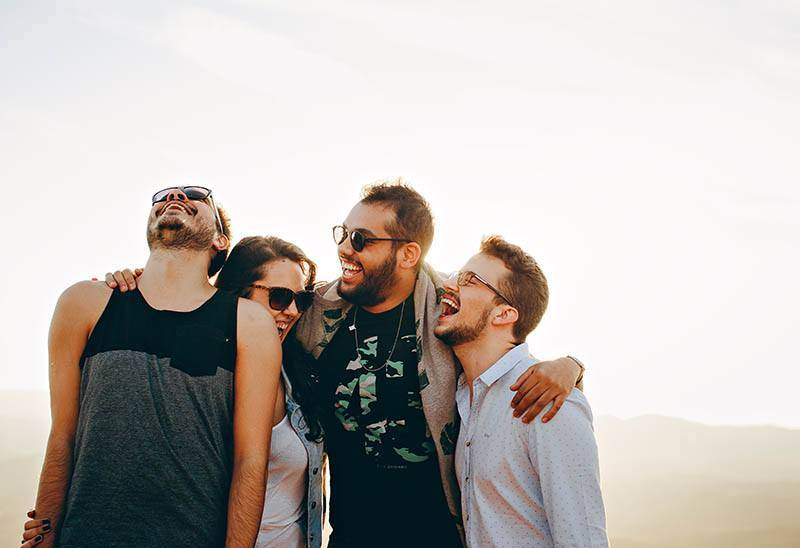 three male and one woman smiling outside