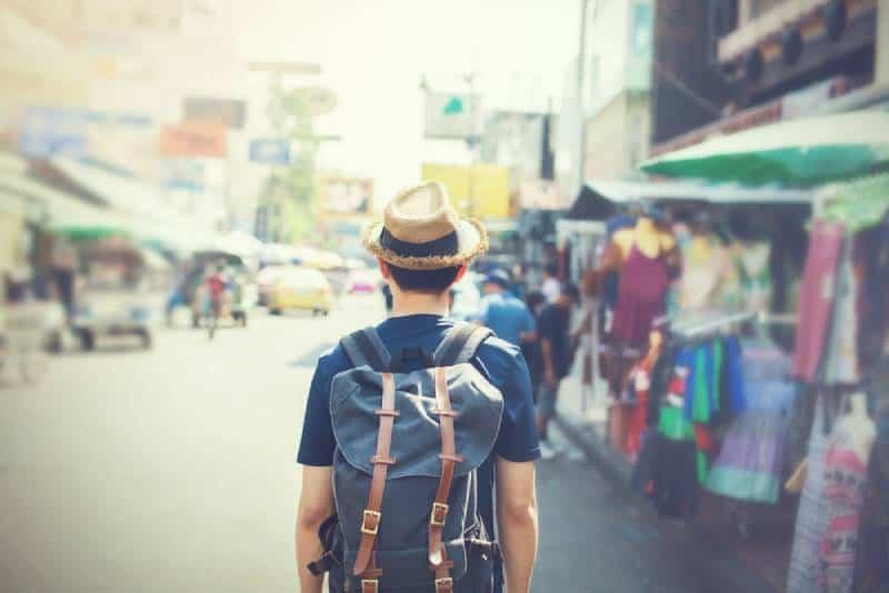 tourist with hat walking through outdoor market