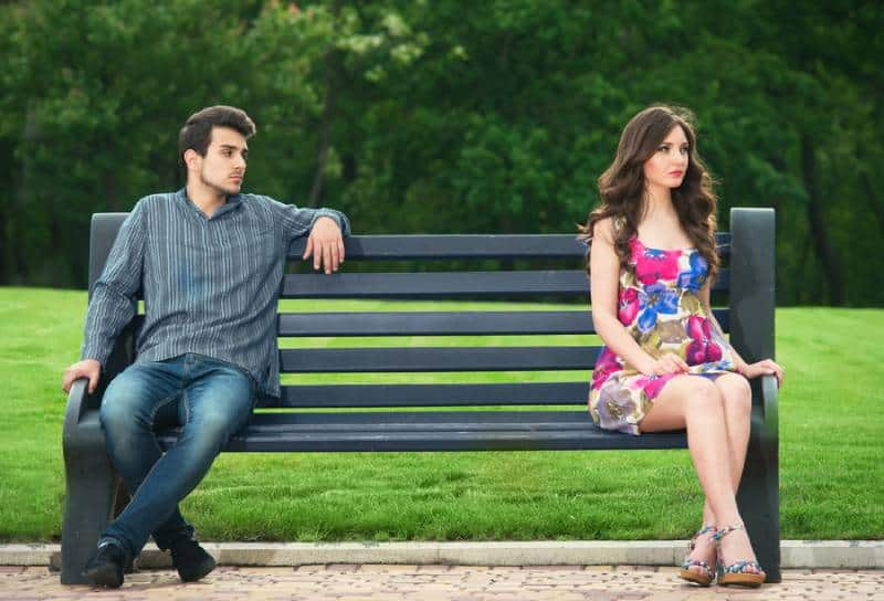 unhappy couple sitting on the bench in the park