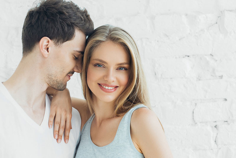 man in love standing with smiling woman
