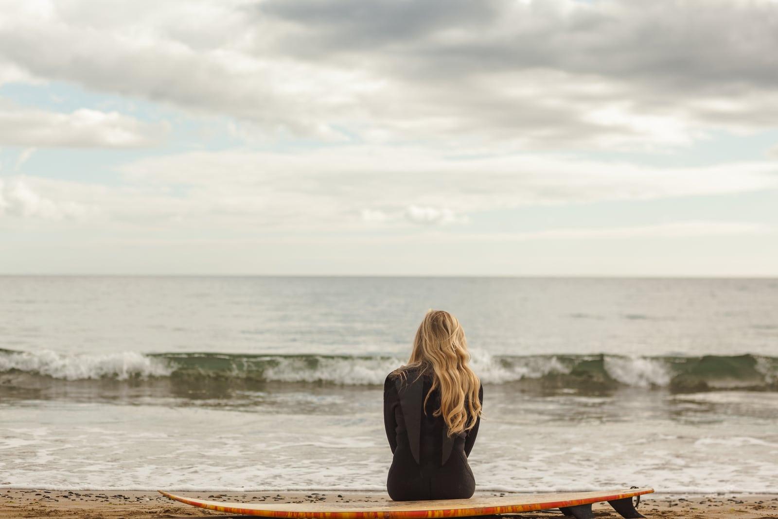 a sad woman sitting by the sea