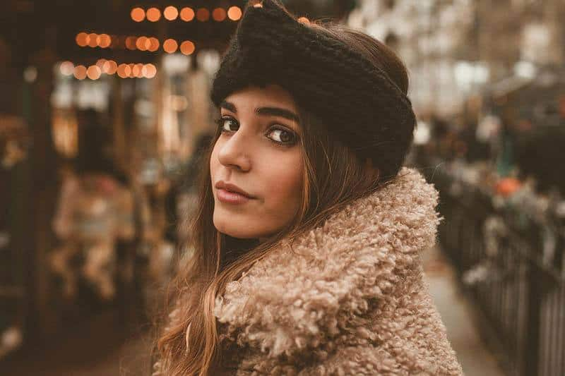 beautiful young brunette wearing hat and brown jacket outside