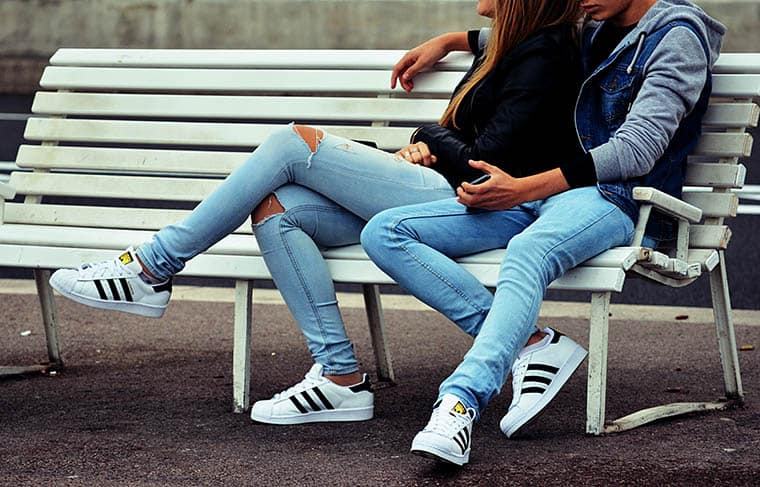 Young same dressed couple sitting on bench