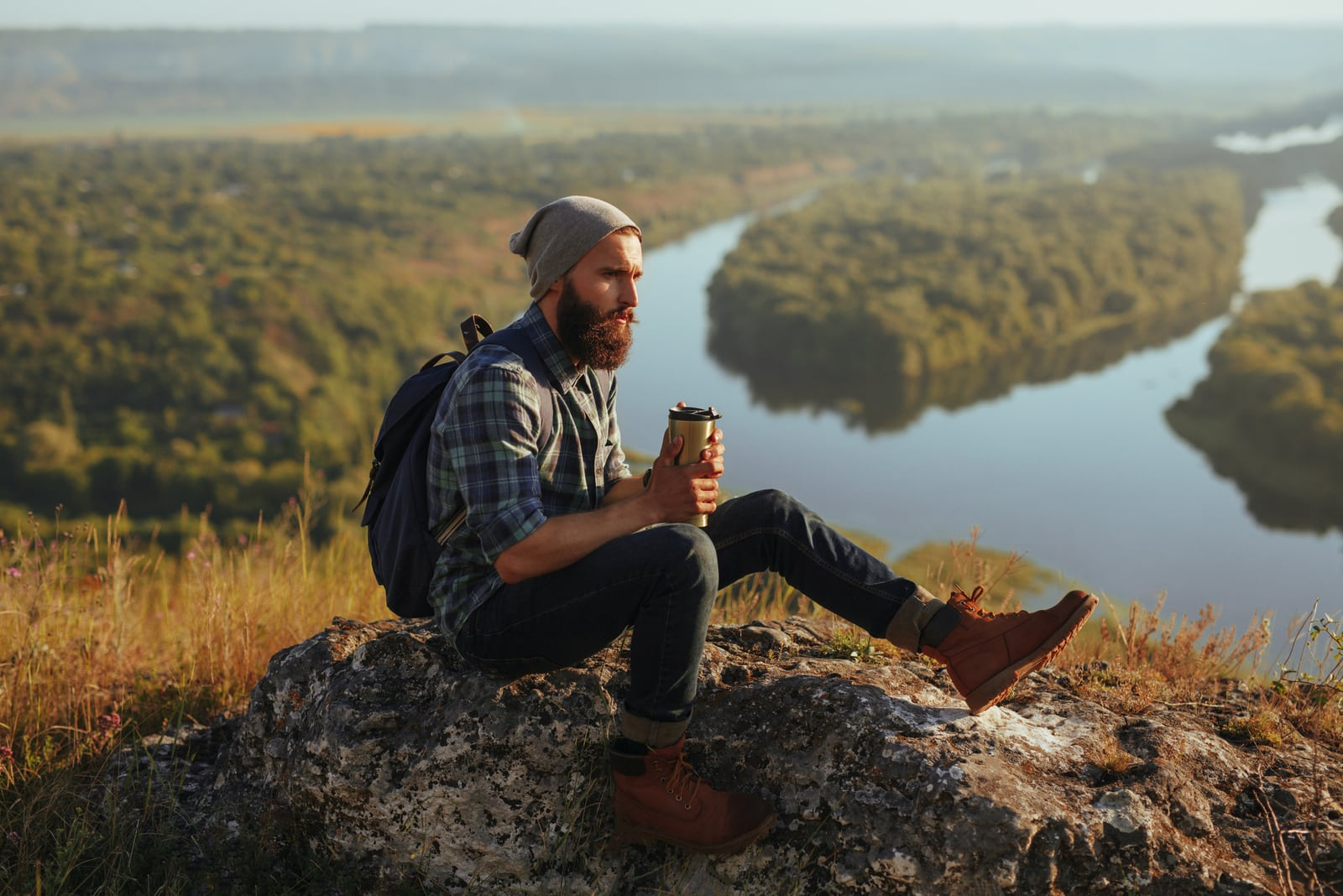man with backpack sitting on the rock