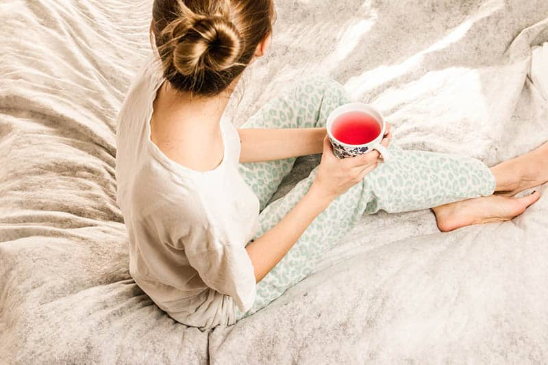 Woman sitting on bed in comfy pajamas holding a cup of tea