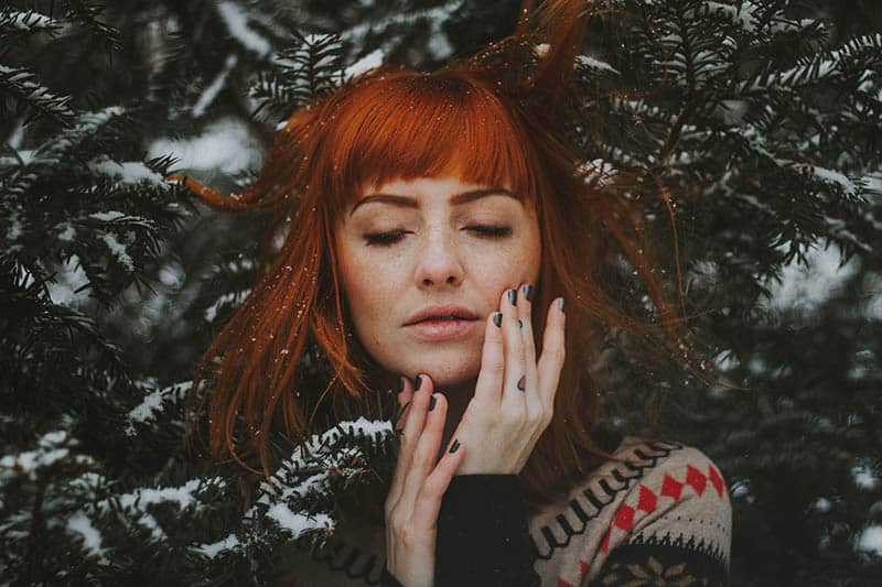 Woman touching her face under a pine